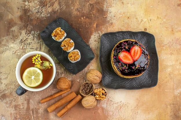 Bovenaanzicht lekkere zoete pannenkoeken met kopje thee op licht bureau