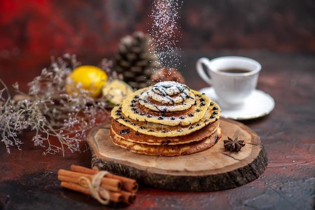 Bovenaanzicht lekkere zoete pannenkoeken met thee op het donkere oppervlak