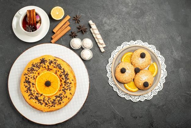 Bovenaanzicht lekkere zoete taart met koekjes en kopje thee op grijze ondergrond zoete taart taart dessert biscuit thee