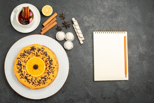 Bovenaanzicht lekkere zoete taart met sinaasappel en kopje thee op het grijze oppervlak zoete taart taart dessert biscuit thee