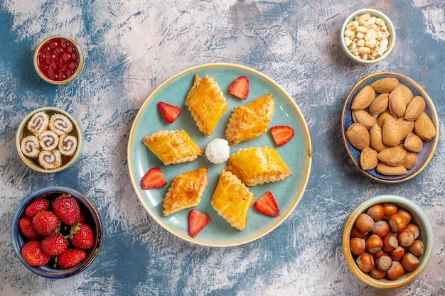 Bovenaanzicht lekkere zoete taarten met noten op blauwe achtergrond
