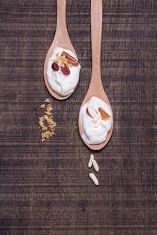 Bovenaanzicht lepels met biologische yoghurt op tafel