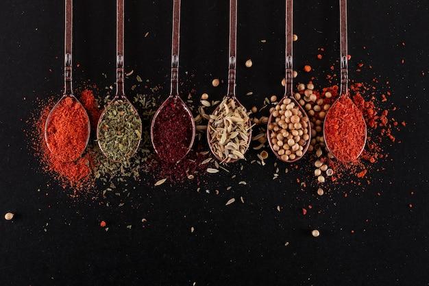 Bovenaanzicht lepels met verschillende peper specerijen op zwarte ondergrond