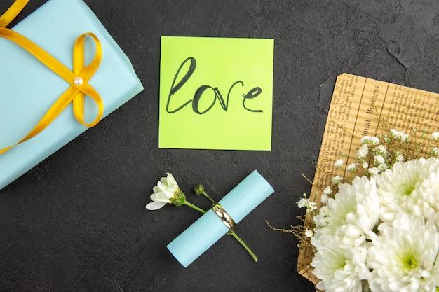 Bovenaanzicht liefde geschreven op groene kleverige nota verlovingsring bloemboeket op donkere achtergrond