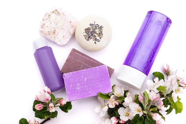 Bovenaanzicht. lila cosmetische flessen, badbom, handgemaakte zeep, badzout met perenbloemen op een witte achtergrond. natuurlijke biologische cosmetica concept. plat leggen