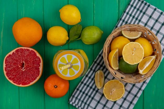 Bovenaanzicht limoen plakjes met citroenen in een mand op een geruite handdoek met sinaasappels en een halve grapefruit op een groene achtergrond
