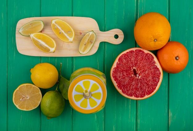 Bovenaanzicht limoen plakjes met citroenen op een snijplank met sinaasappels en een halve grapefruit op een groene achtergrond