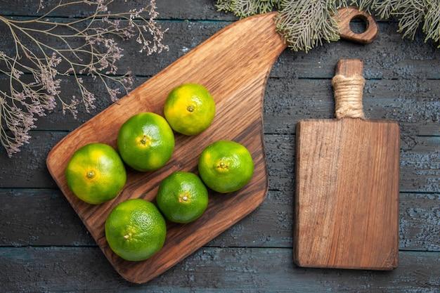 Bovenaanzicht limoenen aan boord zes limoenen op keukenplank op tafel naast de snijplank
