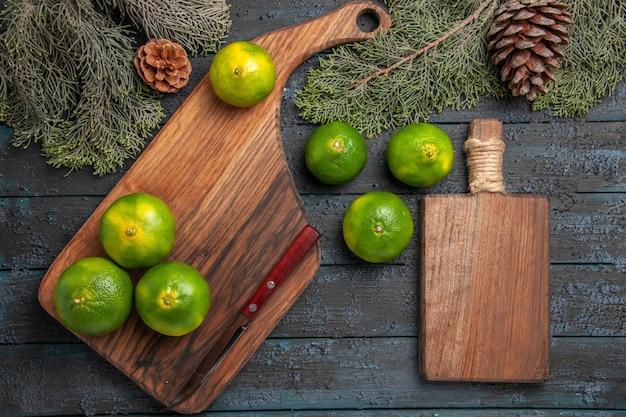 Bovenaanzicht limoenen en takken vier groengele limoenen en mes op de snijplank naast de limoenen keukenbord en boomtakken en kegels