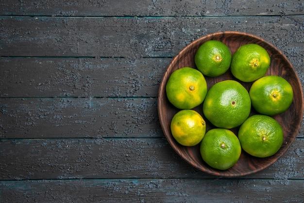 Bovenaanzicht limoenen in kom groene limoenen in houten kom op de grijze achtergrond