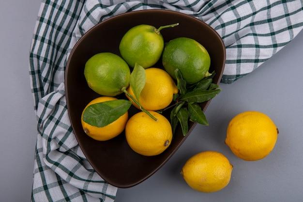 Bovenaanzicht limoenen (lemmetjes) met citroenen in een kom op een geruite handdoek op een grijze achtergrond