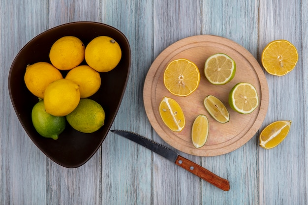 Bovenaanzicht limoenen (lemmetjes) met citroenen in kom en wiggen op snijplank met mes op grijze achtergrond