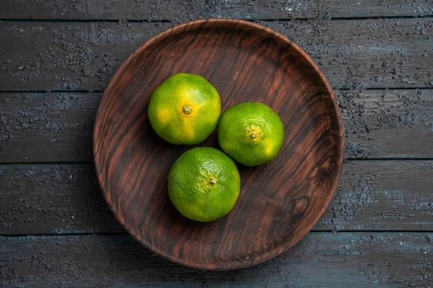 Bovenaanzicht limoenen op plaat van drie limoenen in het midden van de donkere tafel