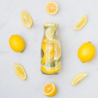 Bovenaanzicht limonade omgeven door citroenen