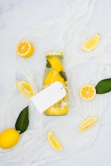 Bovenaanzicht limonadefles met citroenen