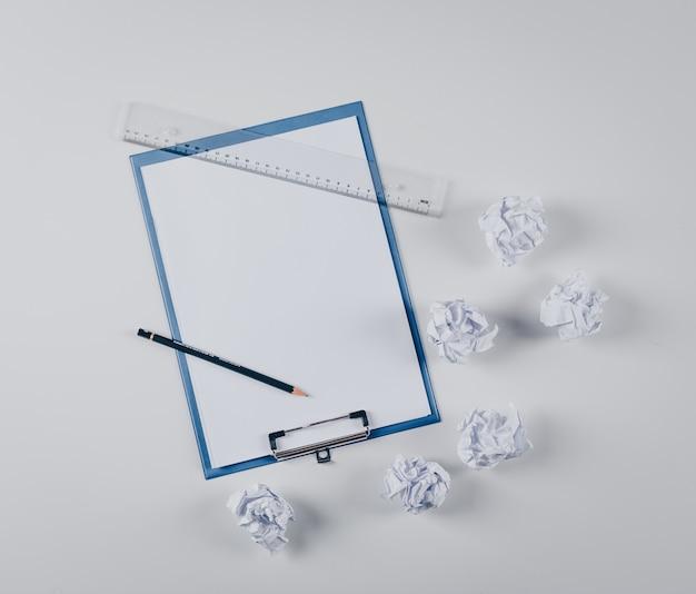 Bovenaanzicht liniaal en potlood op klembord met verfrommeld papier op wit