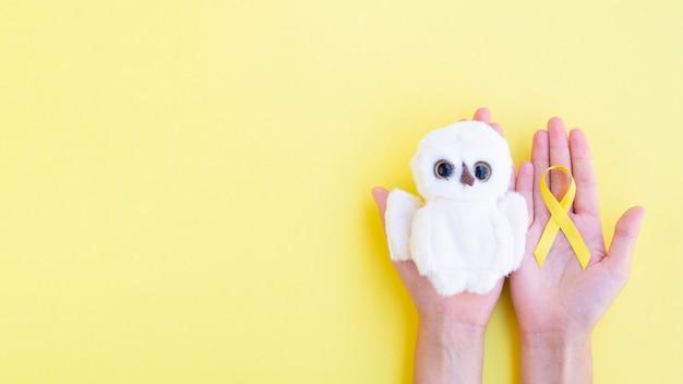 Bovenaanzicht lint en speelgoed met gele achtergrond