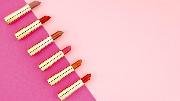 Bovenaanzicht lippenstiften op kleurrijke achtergrond met kopie ruimte