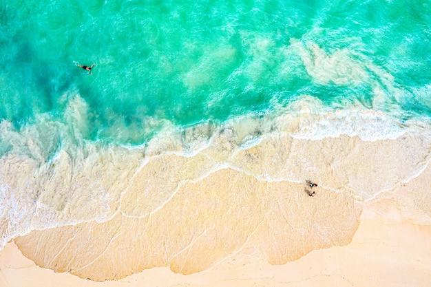 Bovenaanzicht luchtfoto drone foto van oceaan kust met prachtig turquoise water, schuim zee golven en mensen. caribische badplaats. vakantie reizen achtergrond.