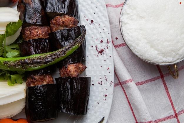 Bovenaanzicht lula kabab met aubergine met gebakken groenten en gehakte ui en ayran in houten voedsel lade