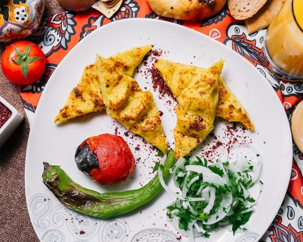 Bovenaanzicht lula kebab aardappelen met tomaat en gegrilde peper met uien en kruiden