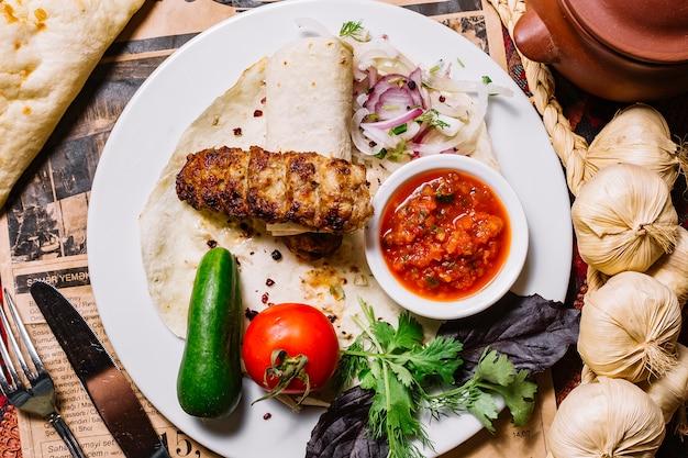 Bovenaanzicht lula kebab in pitabroodje met groenten en saus