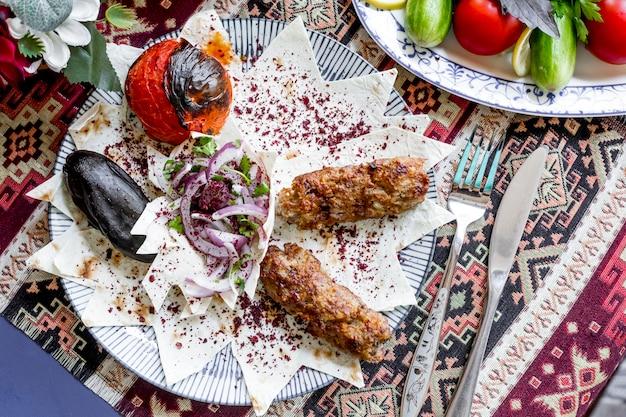 Bovenaanzicht lula kebab op pitabroodje met aubergine en tomaat gegrild met uien