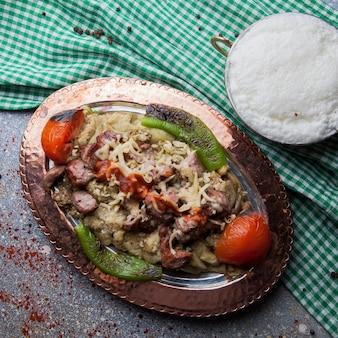 Bovenaanzicht lule kebab gemengde auberginesalade met tomaat en papier en ayran