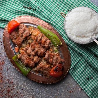 Bovenaanzicht lule kebab onder auberginesalade met tomaat en papier en ayran