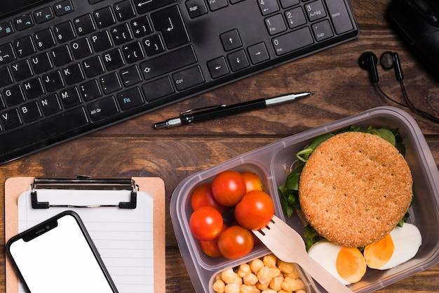 Bovenaanzicht lunchbox en toetsenbord met lege notebook en telefoon