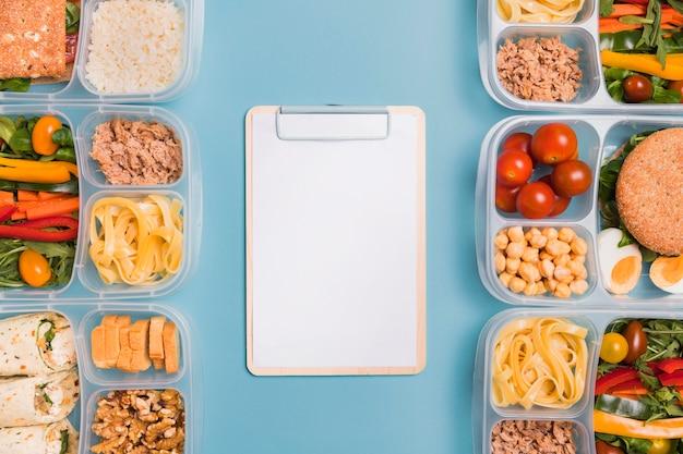 Bovenaanzicht lunchboxen met lege notebook