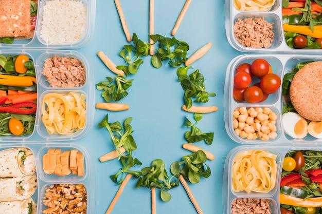 Bovenaanzicht lunchdozen met soepstengels en bladeren