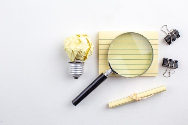 Bovenaanzicht lupa op plaknotitie bindmiddel clips opgerold papier vastgebonden met touw op witte tafel