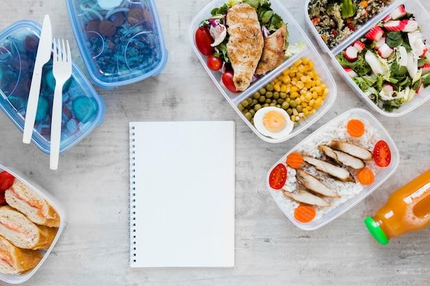 Bovenaanzicht maaltijd containers met notebook