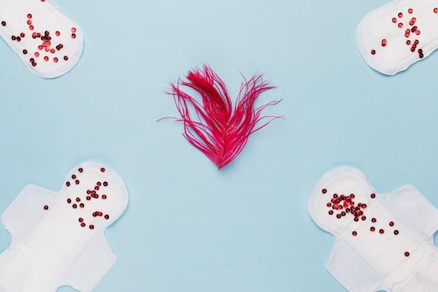 Bovenaanzicht maandverband met rode pailletten en veren