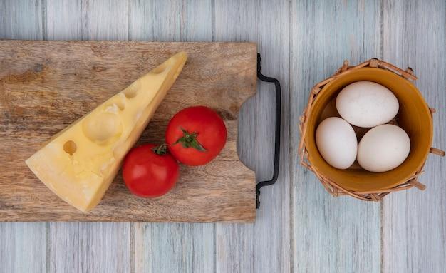 Bovenaanzicht maasdam kaas met tomaten op een standaard en kippeneieren in een mand op een grijze achtergrond