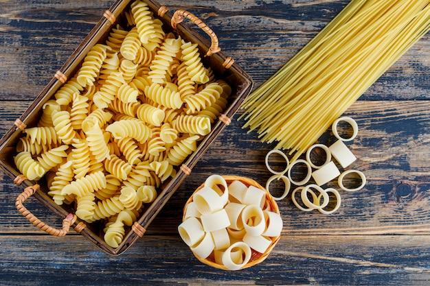 Bovenaanzicht macaroni in mand en emmer met pasta en spaghetti op donkere houten achtergrond. horizontaal