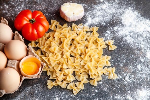 Bovenaanzicht macaroni met eieren, tomaten en knoflook op donkere gestructureerde achtergrond.