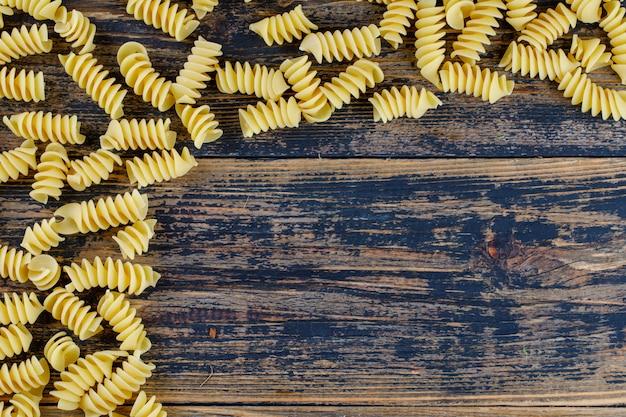 Bovenaanzicht macaroni op donkere houten achtergrond. horizontale ruimte voor tekst