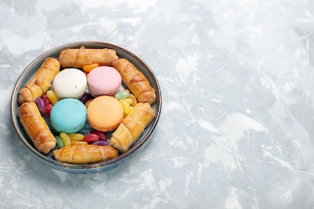Bovenaanzicht macarons en bagels in lade op wit