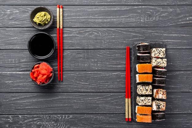 Bovenaanzicht maki sushi assortiment op leisteen met stokjes