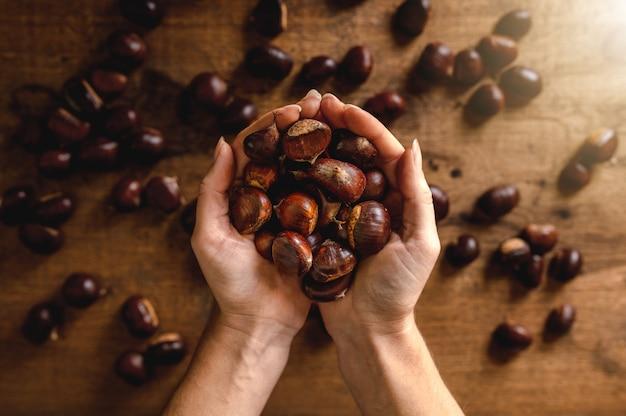 Bovenaanzicht man beide handen met kastanjes, houten tafel achtergrond met meer fruit.
