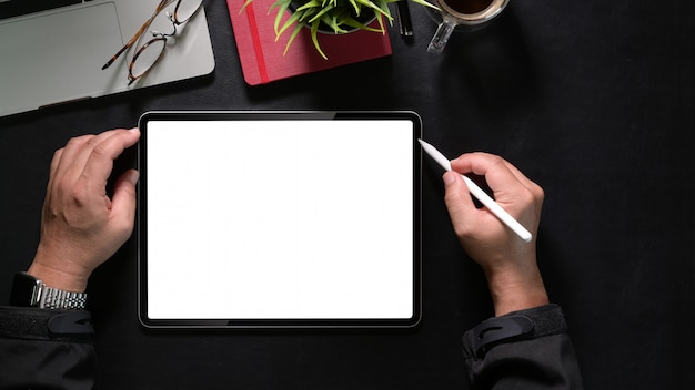 Bovenaanzicht man hand tekening tablet en potloden, mockup leeg scherm tablet