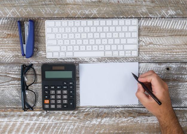 Bovenaanzicht man iets schrijven op papier, met toetsenbord, brillen, pen, cactus, vergrootglas op houten achtergrond. horizontaal