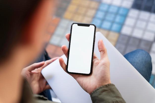 Bovenaanzicht man kijkt naar zijn telefoon met een leeg scherm