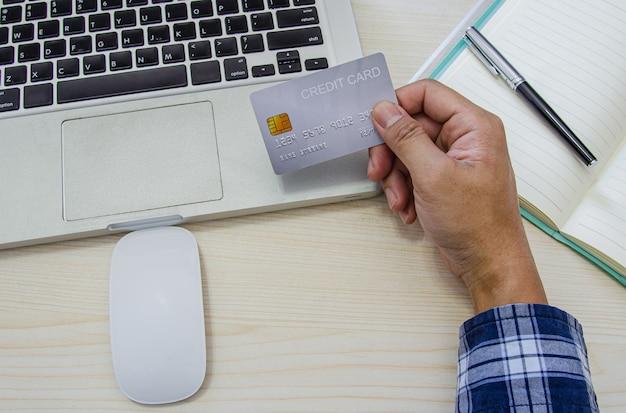 Bovenaanzicht man met een creditcard en het dragen van een blauw geruite hemd op het bureau. laptop computer kladblok en pen. online winkelen, betalen met creditcard