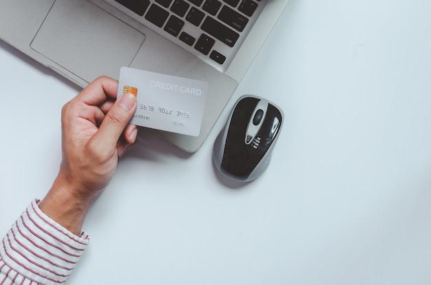 Bovenaanzicht man met een creditcard en op het bureau. laptop computer kladblok en pen. online winkelen, betalen met creditcard