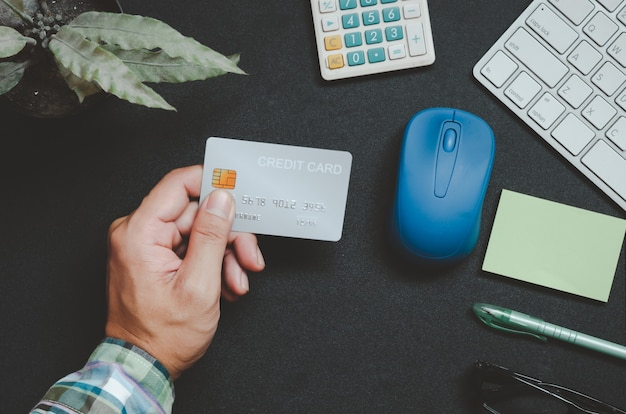 Bovenaanzicht man met een creditcard en op het bureau