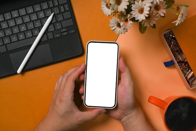 Bovenaanzicht man met mock-up mobiele telefoon met leeg display.