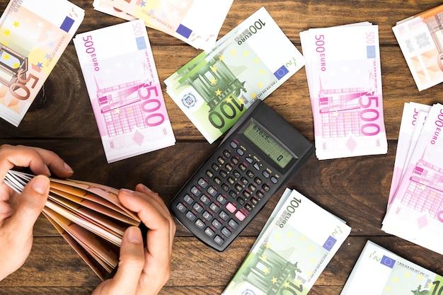 Bovenaanzicht man tellen van geld met calculator